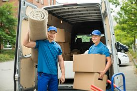 stock photo of moving van  - Two Male Workers Carrying Carpet And Cardboard Boxes In Front Of Van - JPG