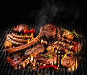 Assorted delicious grilled meat with vegetables over the coals on a barbecue poster
