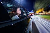 Moving towards the nightlife in the city, woman on the backseat of a car poster