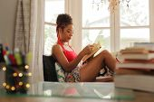 African American Woman Reading Book At Home Near Window poster