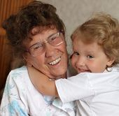Happy pro-grandmother with the granddaughter at home