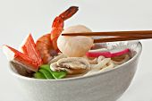 Seafood Udon Noodle Soup, Popular Japanese Dish, with shrimp, crabmeat, scallop, fish cake, snow pea