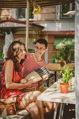 Young Beautiful Happy Loving Couple Sitting At Street Open-air Cafe, Having Fun With Pillow. Beginni poster