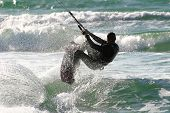 Unidentified kitesurfer jumps over the water during surfing on Mediterranean Sea.