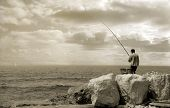 Old fisherman standing on the breakwater with fishing rod (sepia toned).