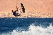 EILAT, ISRAEL - MARCH 31: Unidentified kitesurfer jumps over the water during surfing on Red Sea Mar