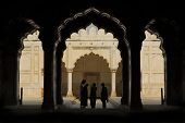 silhouettes of people under the arches at the red fort in delhi, india