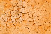 Orange bursted dry hard sand in desert
