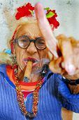 HAVANA â?? CIRCA DECEMBER 2008: An eccentric old Cuban lady smokes cigar and points finger circa Dec