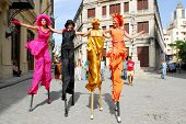 HAVANA - CIRCA DEC 2008 : Colorful Cuban girls dance on stilts and entertain tourists circa December