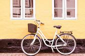 Vintage bike with basket against wall in Denmark in sepia tone