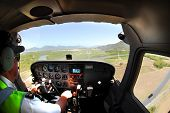 Pilot landing a small plane on Cairns airport, Australia after scenic flight