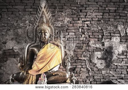 poster of Big Buddha Statue At Brick Wall Background. Metal Sculpture, Buddha Statue To Worship.
