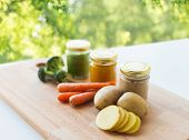 baby food, healthy eating and nutrition concept - vegetable puree in glass jars on wooden board over poster