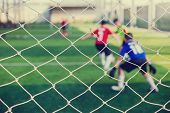 Mesh Of Goal With Blurry Of Soccer Goalkeeper And Soccer Players poster