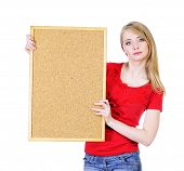 Young blond woman holding a cork board