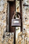 Abandoned Building, With A Fiberboard Gate Closed With A Padlock In The Foreground - Focus On The Pa poster