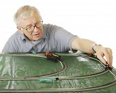 A senior man placing an engine on the track as he sets up a new N-gauge train set.  Focus is on the