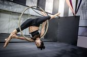 Asian Gymnast Girl Doing Her Gymnastics Performance On Aerial Hoop Or Aerial Ring In Fitness Gym. poster