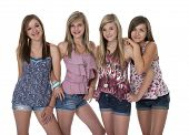 Studio photo of four pretty teenage girls in tight group on white.