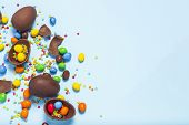 Broken And Whole Chocolate Easter Eggs, Multicolored Sweets On Blue Background. Concept Of Celebrati poster