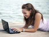Young beautiful woman working outdoors with her laptop