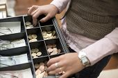 Saleswoman hands at cash register with euro coins and notes