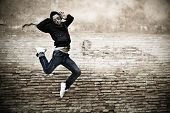 stock photo of break-dance  - Young attractive man dancing in urban background - JPG