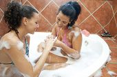 Two happy young girls applying nailpaints while having a bath