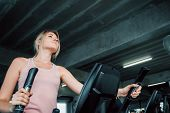 Portrait Of Sporty Woman Exercising Elliptical In Fitness Gym., Group Of Pretty Women In Sportswear  poster
