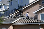 stock photo of roof tile  - Hispanic roofer laying roofing tile on a newly constructed house - JPG