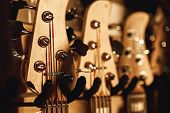 Uppermost Part Of The Guitar. Close View Of Several Acoustic Guitar Headstocks With Tuning Keys For  poster