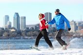 Happy couple snowshoeing running in montreal with cityscape skyline and river st. Lawrence in backgr