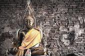 Big Buddha Statue At Brick Wall Background. Metal Sculpture, Buddha Statue To Worship. poster