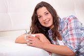 stock photo of futon  - Woman drinking hot drink - JPG