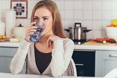 Woman sitting in kitchen and drinking mineral water from glass. poster