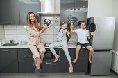 Young woman and her children are sitting on the kitchen set and playing with kitchen utensils at the poster