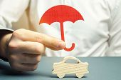 Insurance Agent Holding An Umbrella Over A Miniature Wooden Car. Auto Insurance Concept. Insurance C poster