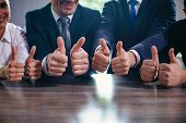 Cropped Image Of Businessmen Holding Their Big Thumbs Up While Sitting In A Row. Selective Focus On  poster