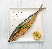 Baked Whole Fish Grilled On A Plate With Vegetables And Lemon poster