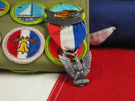 stock photo of boy scout  - Macro shot of Eagle Scout Award laying on an American Flag - JPG