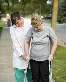 stock photo of physical therapist  - physical therapist helps a woman on crutches - JPG