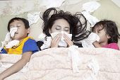 picture of blowing nose  - Family is lying on a bed due to flu in winter - JPG