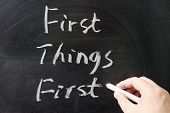 picture of proverb  - First things first words written on the chalkboard - JPG