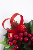 stock photo of winterberry  - Detail of Christmas wreath with winterberries red ribbon and green leaves over white - JPG