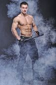 stock photo of policeman  - Good Looking Policeman Bodybuilder Posing in smoke - JPG