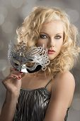 stock photo of turn-up  - pretty blonde girl with curly hair takes one silver mask her body is turned of three quarters at left she looks in to the lens and takes the mask with right hand - JPG