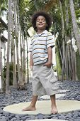 Full length portrait of happy little boy with hands in pockets on stepping stone