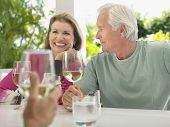 Happy middle aged couple having wine with friend at verandah table