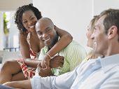 Dois casal multiétnico alegre conversando em casa